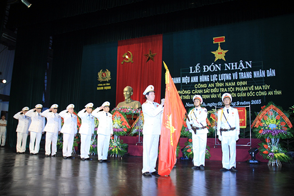 Bộ trưởng Trần Đại Quang gắn huy hiệu Anh hùng LLVTND thời kỳ kháng chiến chống Mỹ lên Cờ truyền thống của Công an tỉnh Nam Định.