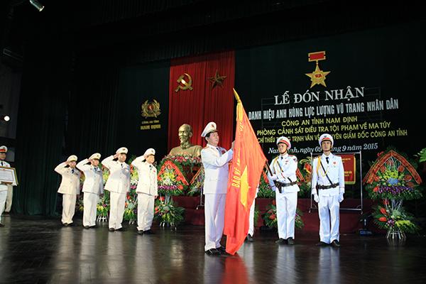 Bộ trưởng Trần Đại Quang gắn Huy hiệu Anh hùng LLVTND thời kỳ đổi mới lên cờ truyền thống Phòng Cảnh sát điều tra tội phạm về ma túy, Công an tỉnh Nam Định.