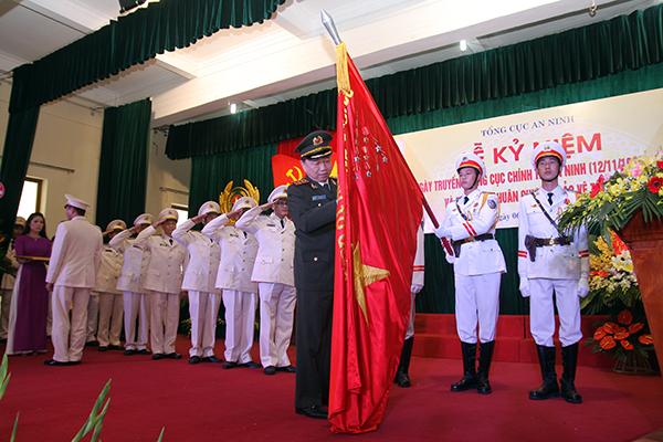 Thứ trưởng Tô Lâm gắn Huân chương Bảo vệ Tổ quốc hạng Nhì lên Cờ truyền thống Cục Chính trị An ninh. Ảnh Việt Hưng.